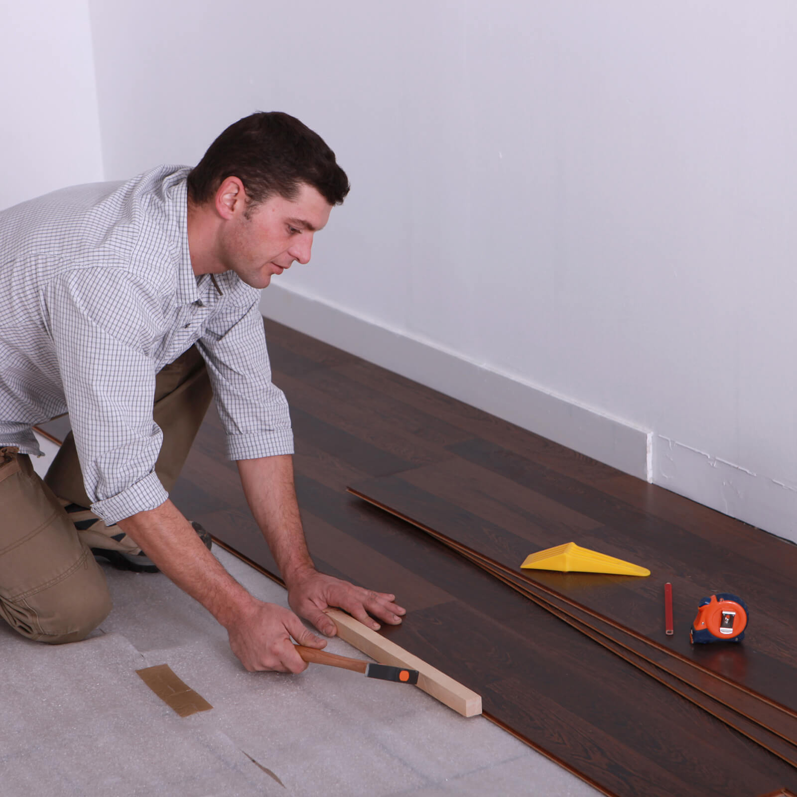 Man installing laminate flooring | Warnike Carpet & Tile